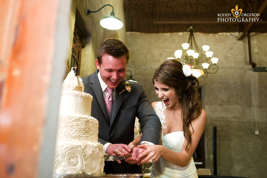 bride and groom cutting the wedding cake during the reception at The Olde Dobbin Station in Texas