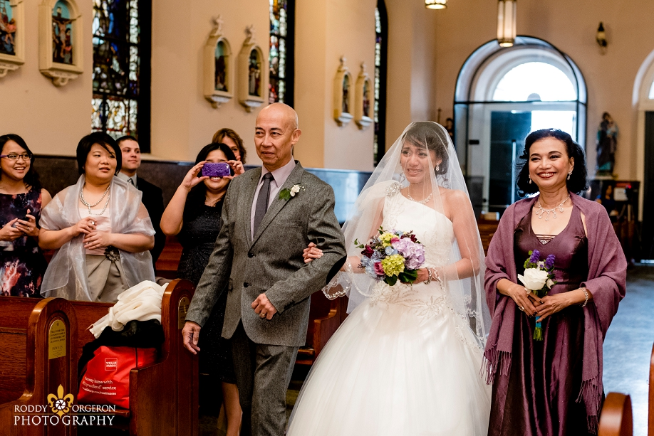 brides mom and dad walks her up the aisle at Our Lady of Guadalupe Church in the French Quarter New Orleans