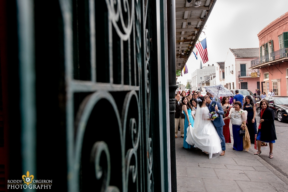 bride and groom second lining and kisssing in the French Quarter New Orleans