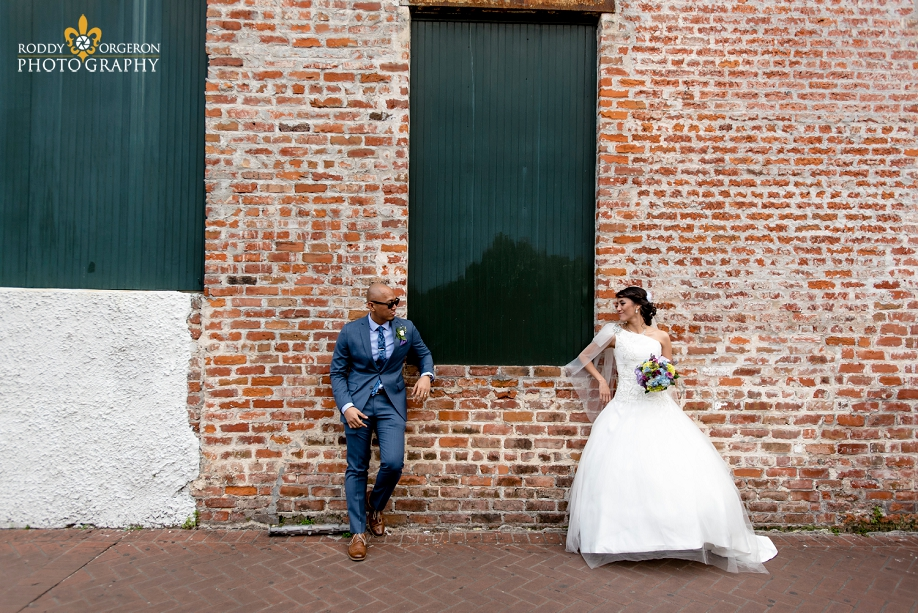 bride and groom posing on a brick wall in the French Quarter New Orleans