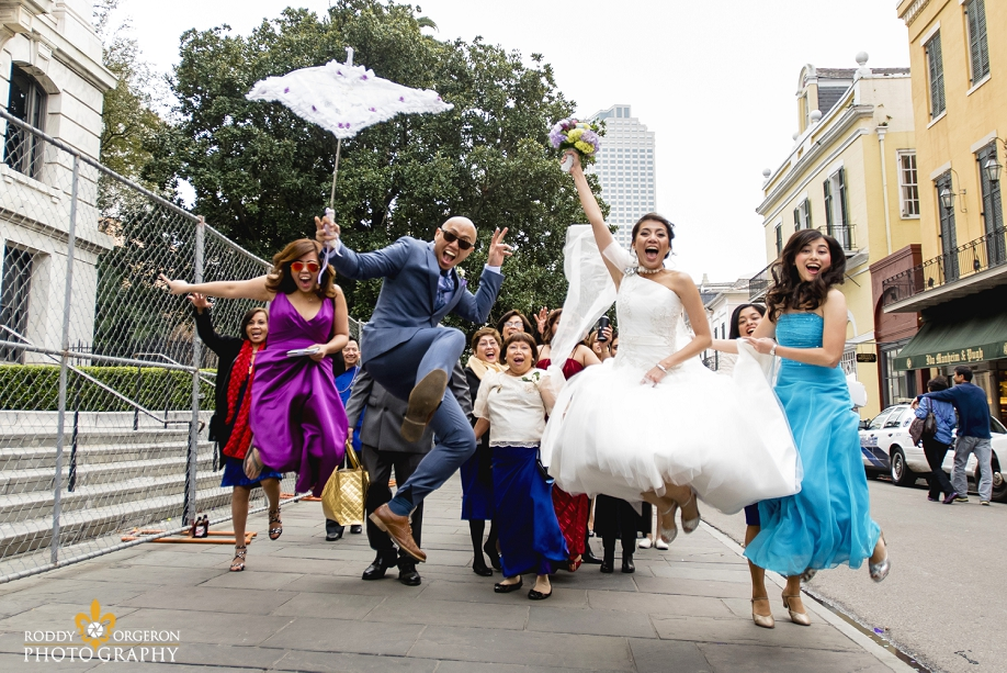 bride and groom jumping in the French Quarter New Orleans