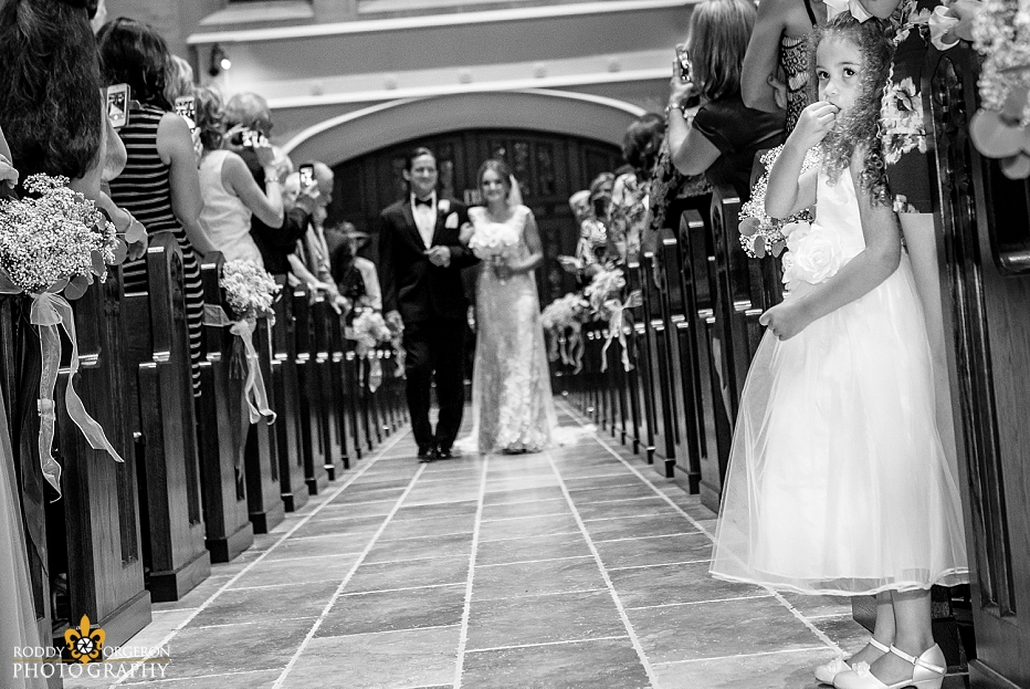 junior bridesmaid looks back at groom as bride walks in the church