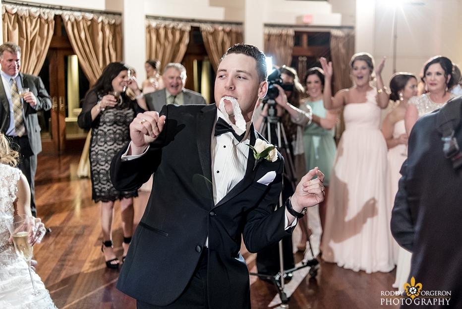 groom dances on the dance floor with the garter at The Audubon Tea Room in New Orleans