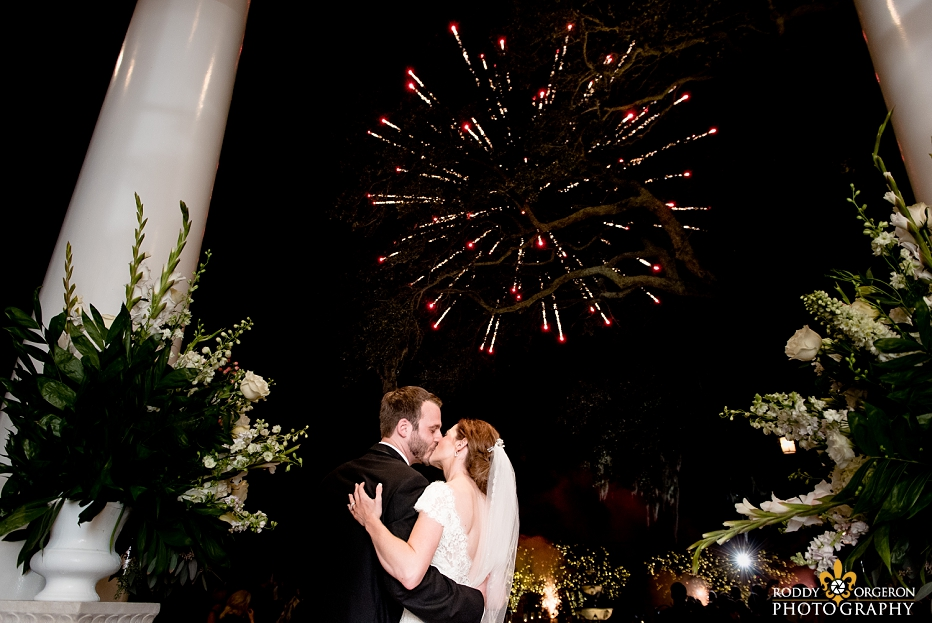 bride and groom kiss at Southern Oaks Plantation with fireworks in the background