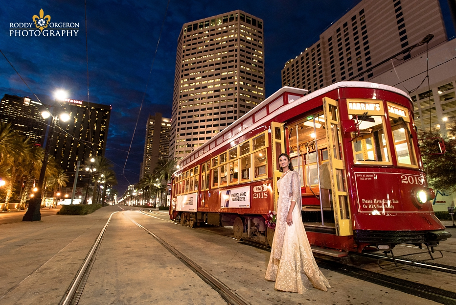 Bride in wedding dress in New Orleans by a street car