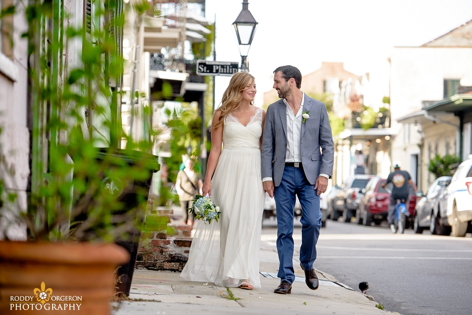 Bride and groom holding hands walking down the street for an engagement session in the French Quarter of New Orleans