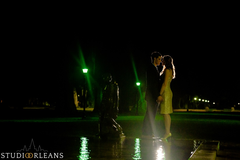 Engaged couple standing in fountain in Audubon Park in New Orleans