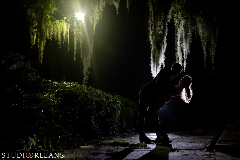 Engaged couple standing under an oak tree in Audubon Park in New Orleans