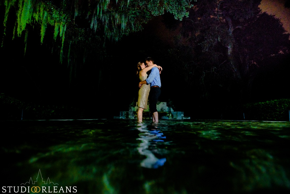 Engaged couple standing under an oak tree in a fountain at Audubon Park in New Orleans