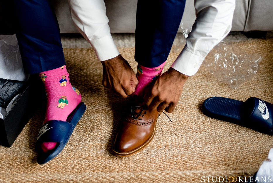 The groom putting his shoes on getting ready for the big day. Photo by Studio Orleans New Orleans Photographers