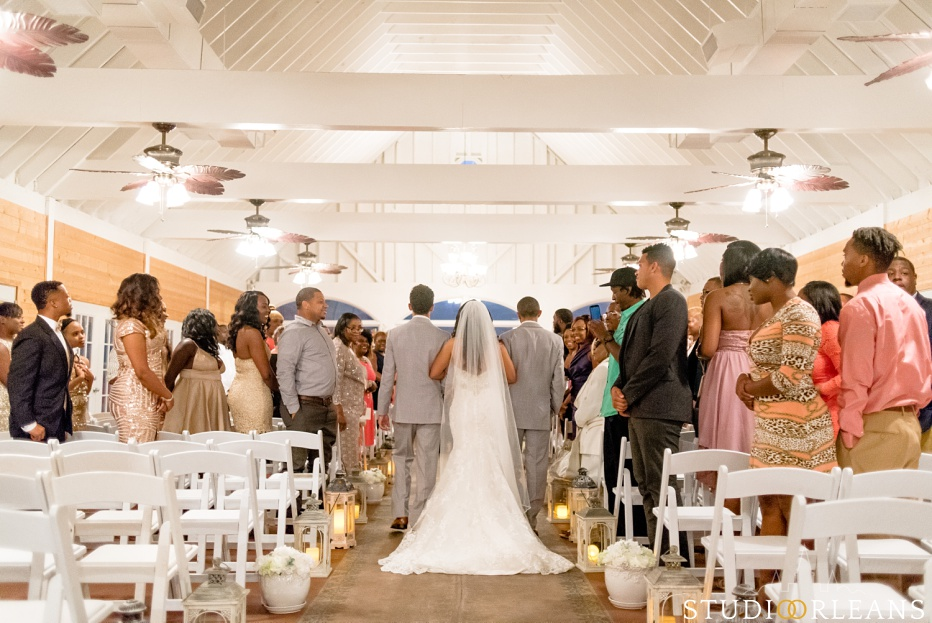 The bride gets escorted down the aisle. This was taken at Cedar Grove Plantation. Photo by Studio Orleans New Orleans Photographers