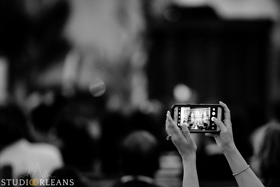 A guest takes a picture of a Bride and groom at the alter at the Saint Louis Cathedral in New Orleans