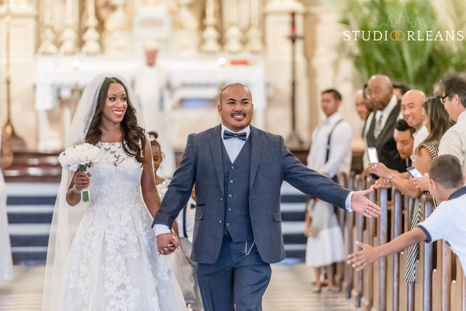 """A bride and groom walk out of the Saint Louis Cathedral after they say """"I Do"""""""