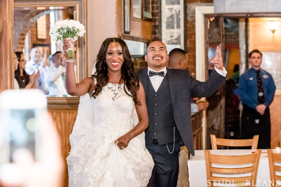The bride and groom make their grand entrance into Oceana Grill in New Orleans