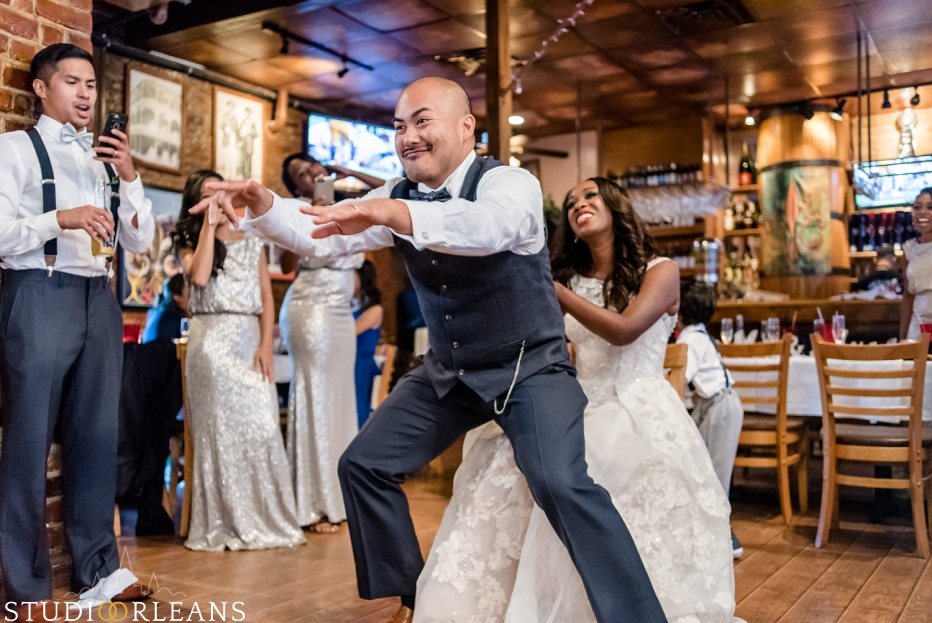The groom dances on his bride acting silly at Oceana Grill in the French Quarter of New Orleans