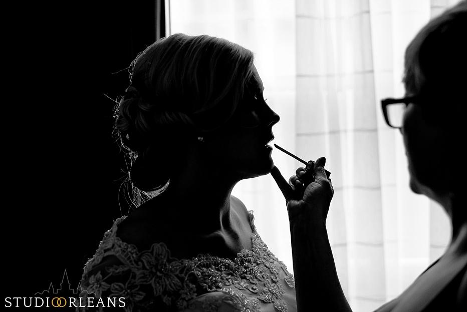 Chateau Lemoyne Wedding - Bride touching up lipstick before the ceremony