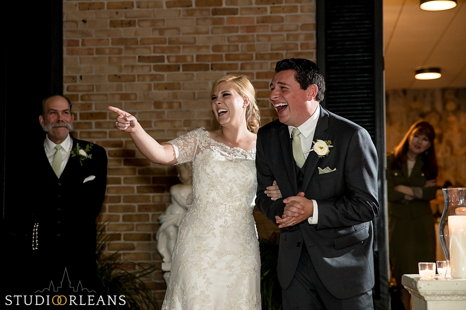 The bride and groom laugh at the best mans speech at the Chateau Lemoyne Courtyard in the French Quarter