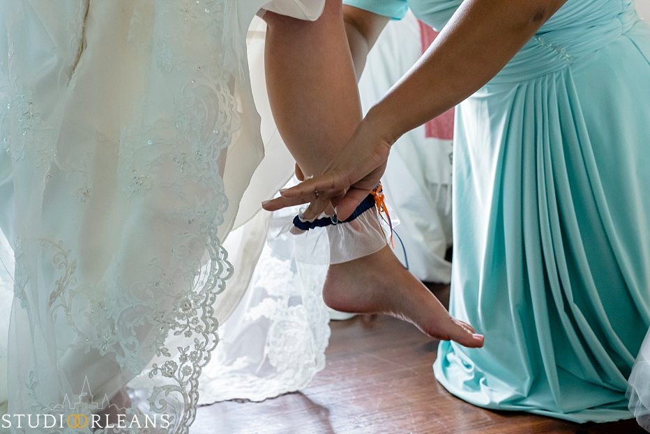 Bridesmaid helping the bride put her garder on before her wedding