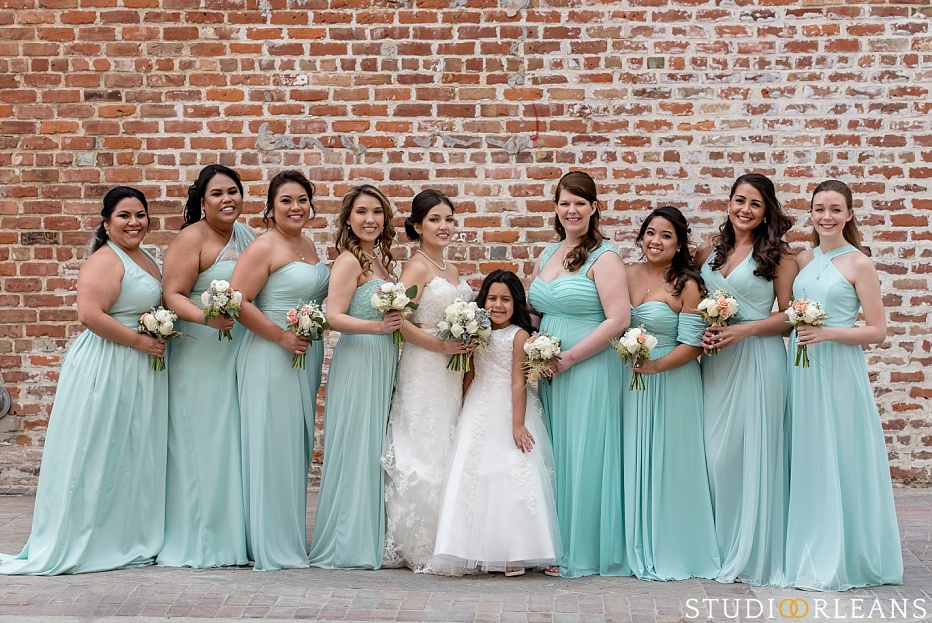 The bride and bridesmaids pose for a picture against this beautiful brick wall in New Orleans