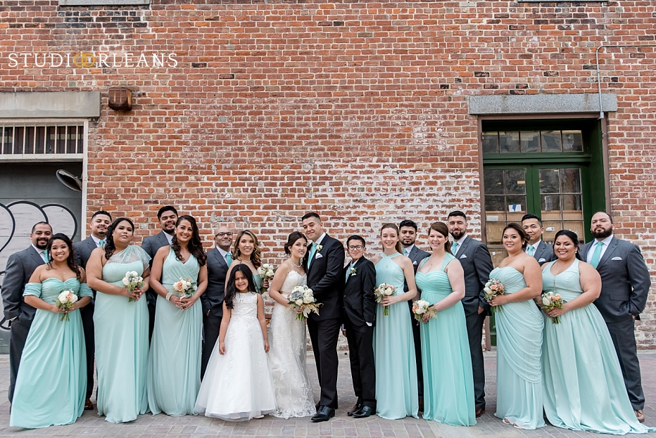 The bridal party pose for a picture against this beautiful brick wall in New Orleans