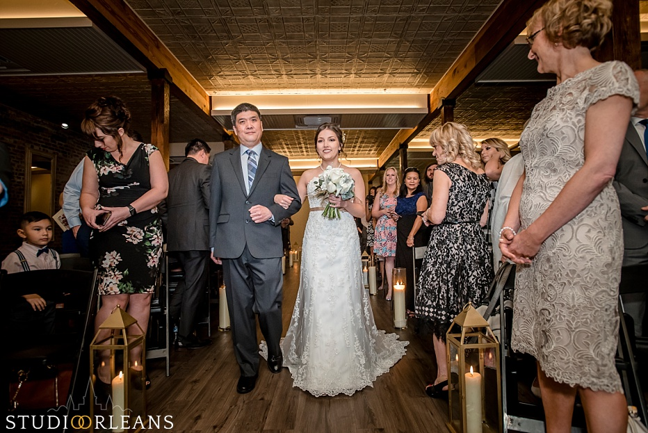 The bride and her father walk down the aisle at The Chicory Wedding venue in New Orleans