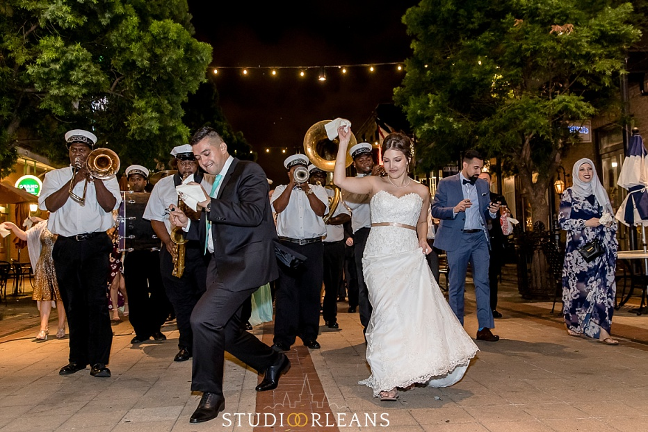 The married couple dances to a second line on Fulton Alley in New Orleans