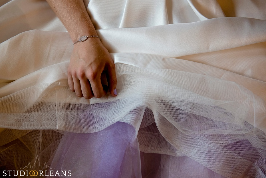 The bride sits down to relax as her mom puts her shoes on before her wedding at the House of Blues in New Orleans