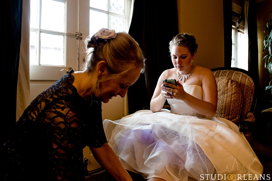 The bride checks her phone as her mom puts her shoes on before her wedding at the House of Blues in New Orleans