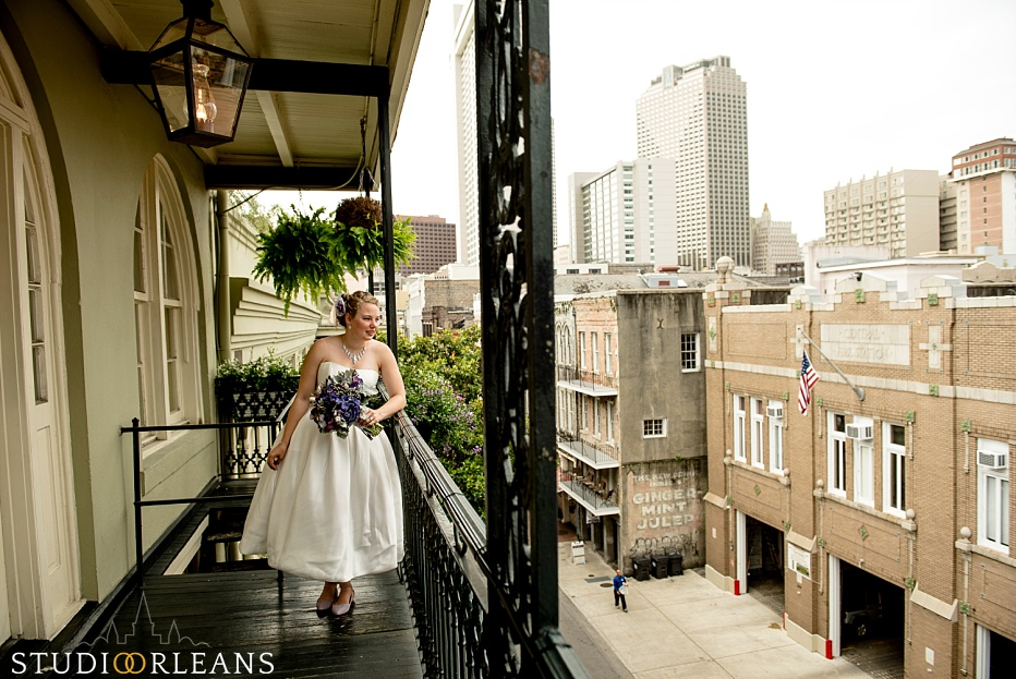 The bride over looks the balcony in the French Quarter of New Orleans before her ceremony